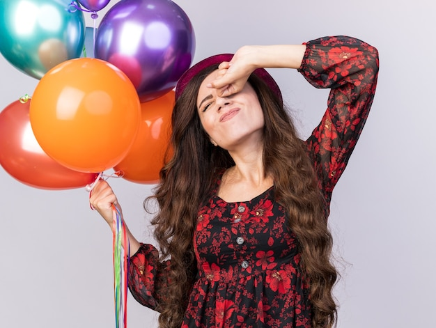 Tired young party girl wearing party hat holding balloons keeping fist on eye stretching with closed eyes isolated on white wall