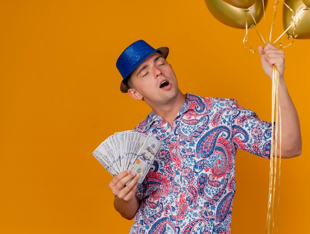 Tired young party guy with closed eyes wearing blue hat holding balloons and cash isolated on orange background with copy space
