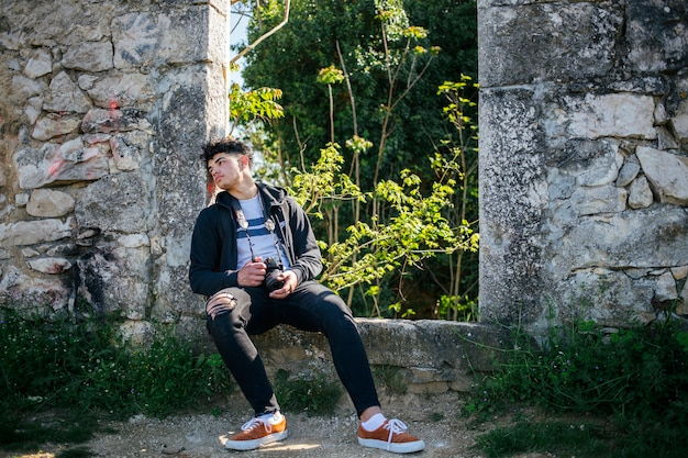 Tired young photographer sitting on old stone wall with holding camera