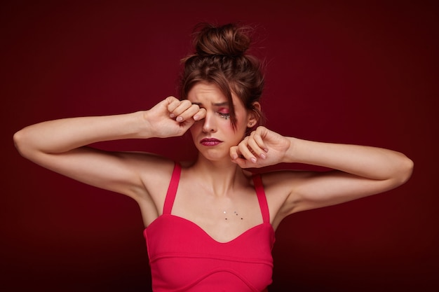 Tired young pretty brunette woman with bun hairstyle raising hands to her face and rubbing her eye wearily, dressed in pink top with straps while standing