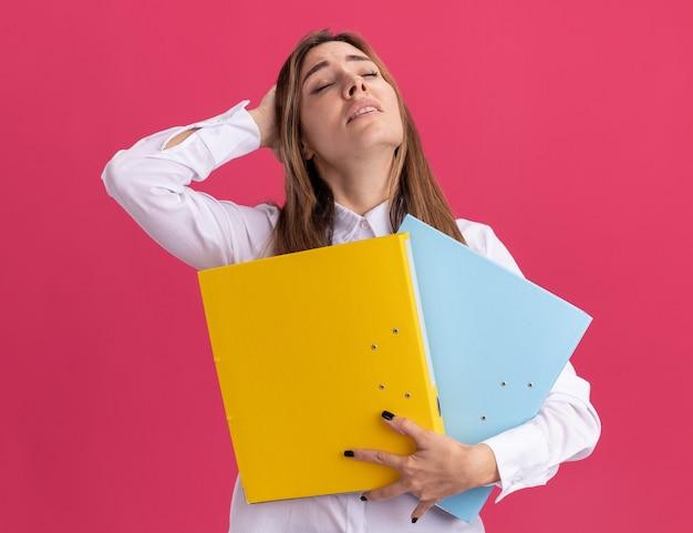 피곤한 젊은 예쁜 백인 여자가 머리에 손을 넣고 파일 폴더를 보유하고 있습니다.