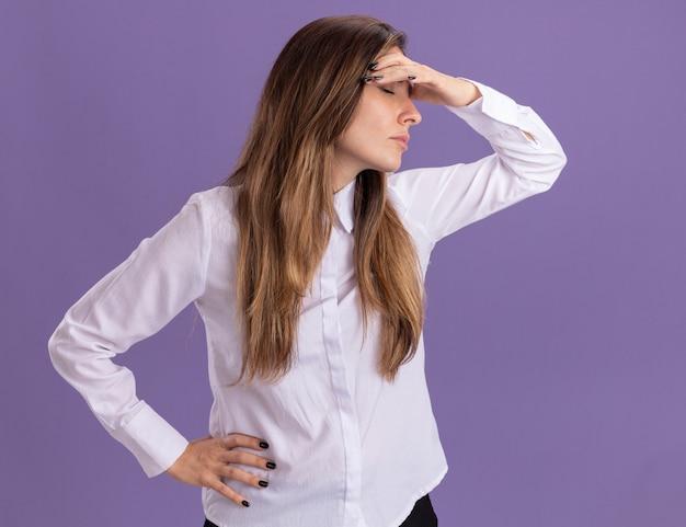 Усталая молодая симпатичная кавказская девушка стоит с закрытыми глазами, положив руку на лоб, изолированную на фиолетовой стене с копией пространства