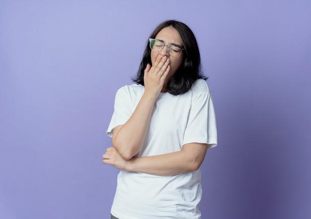 眼鏡をかけて、コピースペースで紫色の背景に分離された目を閉じてあくびをする疲れた若いかなり白人の女の子