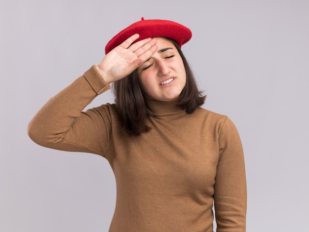 Tired young pretty caucasian girl with beret hat puts hand on forehead