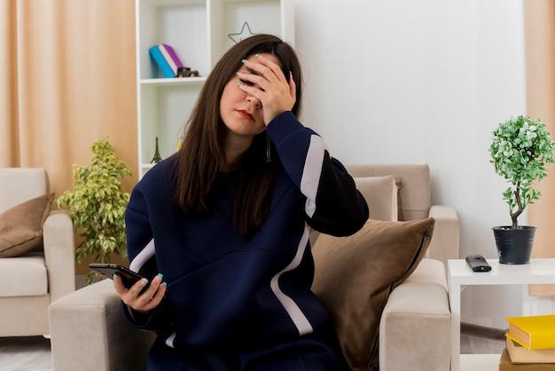 닫힌 된 눈으로 얼굴에 손을 유지 휴대 전화를 들고 설계 거실에서 안락의 자에 앉아 피곤 된 젊은 예쁜 백인 여자