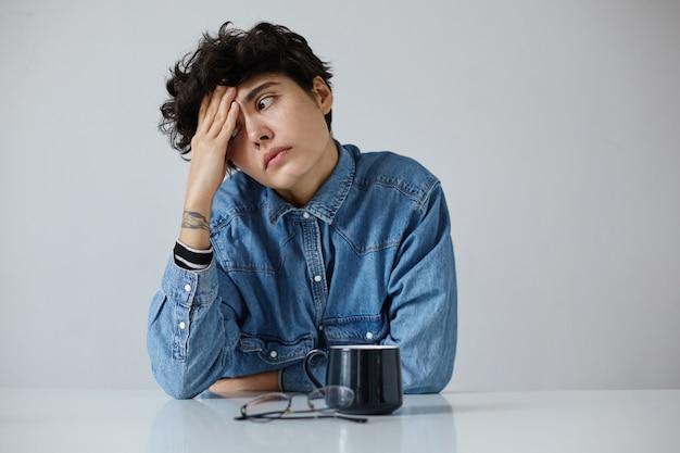 Stanco giovane donna bruna piuttosto riccia con il tatuaggio che tiene il palmo sulla fronte e guardando stancamente da parte, vestito con abiti casual alla moda mentre posa su sfondo bianco