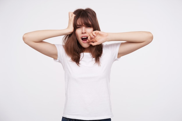 Tired young pretty dark haired lady with casual hairstyle holding palm on her head and covering mouth while yawning, wearing white basic t-shirt while standing over white wall