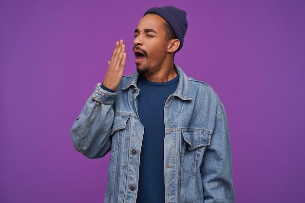 Stanco giovane ragazzo barbuto dalla pelle piuttosto scura che copre la bocca con il palmo sollevato mentre sbadiglia con gli occhi chiusi, vestito con abiti mentre posa sopra il muro viola