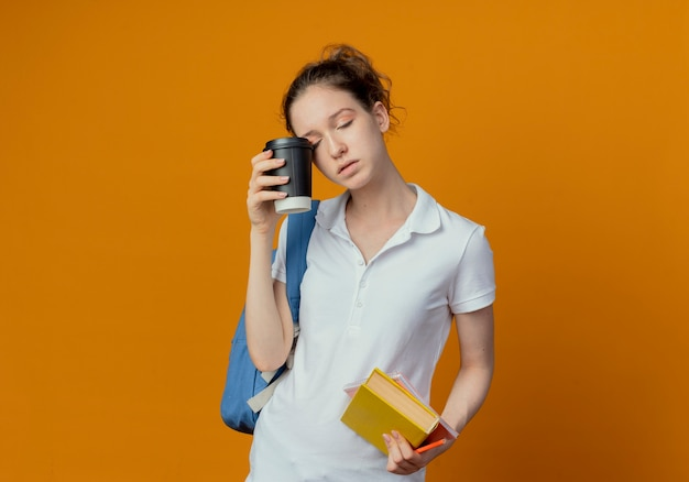 Stanco giovane studentessa graziosa che indossa la borsa posteriore tenendo il libro appunti penna e toccando l'occhio con la tazza di caffè in plastica con gli occhi chiusi isolato su sfondo arancione con spazio di copia