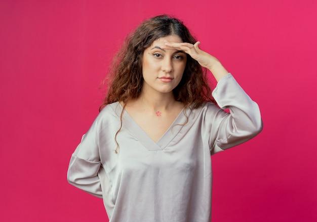 Ragazza graziosa giovane stanca che mette la mano sulla fronte isolata sulla parete rosa