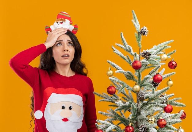 Усталая молодая красивая девушка в повязке на голову санта-клауса и свитере стоит возле украшенной елки, держа руку за голову, глядя вверх изолированно на оранжевом фоне