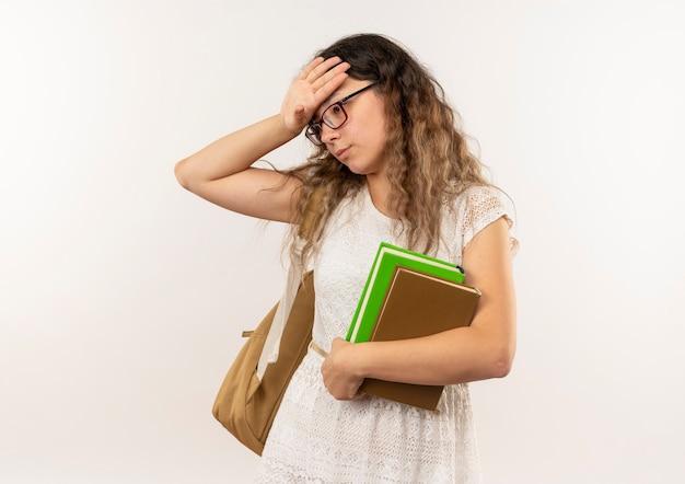 Усталая молодая симпатичная школьница в очках и спине с сумкой, держащая книги, глядя вниз, положив руку на голову, изолированную на белом фоне с копией пространства