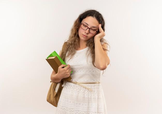 眼鏡とバックバッグを身に着けている疲れた若いかわいい女子高生は、コピースペースで背景に分離された目を閉じて頭に手を置く本を保持します。