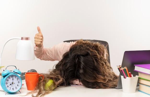 机の上に頭を置き、白い背景で隔離の親指を見せて学校のツールと机に座って眼鏡をかけている疲れた若いかわいい女子高生