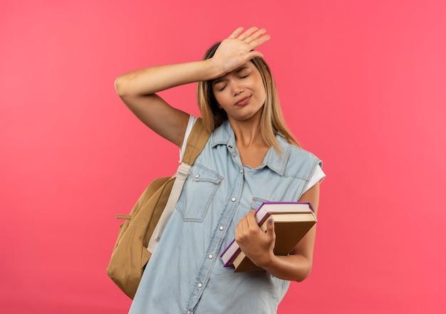 コピースペースでピンクの背景に分離された目を閉じて額に手を置く本を保持しているバックバッグを身に着けている疲れた若いかわいい学生の女の子