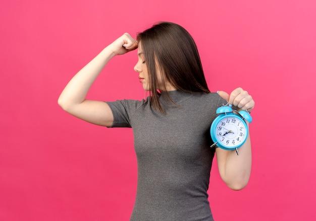 ピンクの背景で隔離の目を閉じて額に拳を置く目覚まし時計を保持している疲れた若いきれいな女性