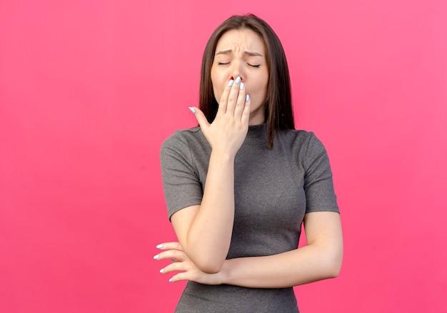 Giovane donna graziosa stanca che mette la mano sotto il gomito e sulla bocca che sbadiglia con gli occhi chiusi isolati su fondo rosa con lo spazio della copia