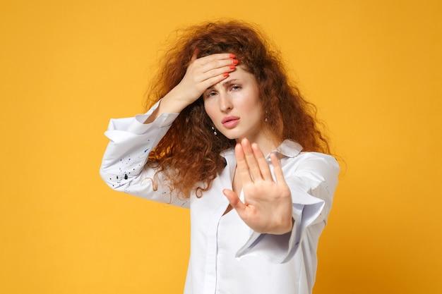 Усталая молодая рыжая девушка в повседневной белой рубашке позирует изолированной на желто-оранжевой стене