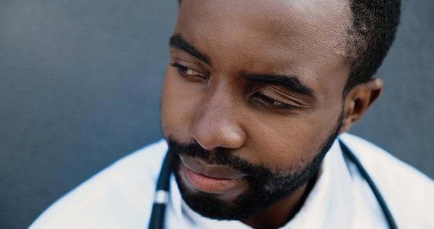 医療マスクを脱いで壁に寄りかかって休んでいる疲れた若い悲しいアフリカ系アメリカ人男性医師。勤勉の後の男性の薬の休息。失われた命。失望した医師の困難な日。閉じる。