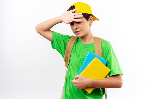 白い壁に隔離された額に手を置く本を保持しているキャップとバックパックを身に着けている疲れた少年