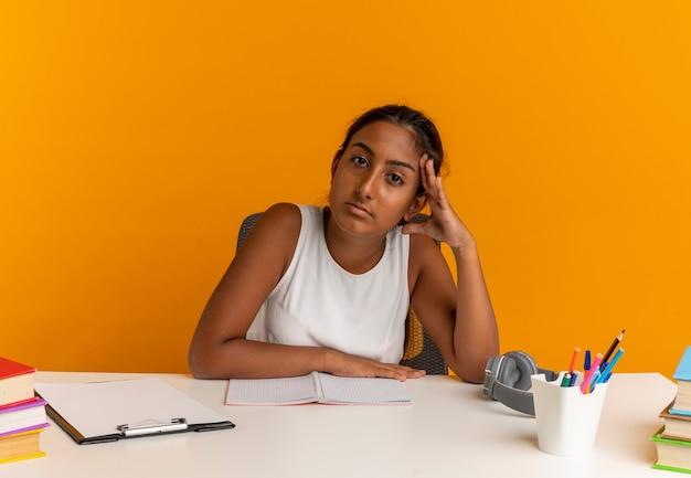 Giovane studentessa stanca che si siede allo scrittorio con gli strumenti della scuola che mette la mano sulla testa sull'arancio