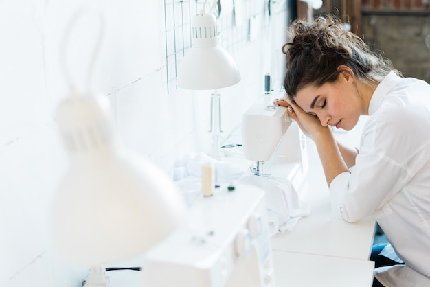 Tired young seamstress with closed eyes leaning on sewing machine while sleeping at workplace