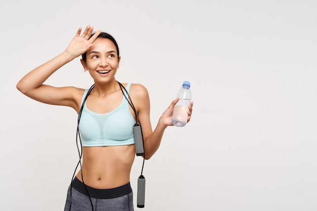 Tired young slim brunette woman with casual hairstyle being happy after nice workout and raising hand to her head, standing over white wall with bottle of water