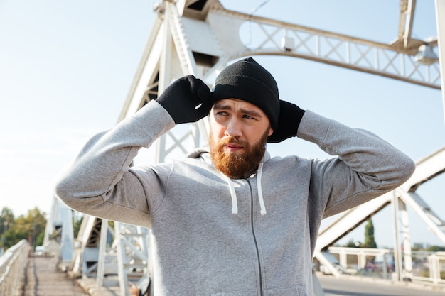 橋の上に立っている間ジョギングの準備をしている帽子の疲れた若いスポーツ男