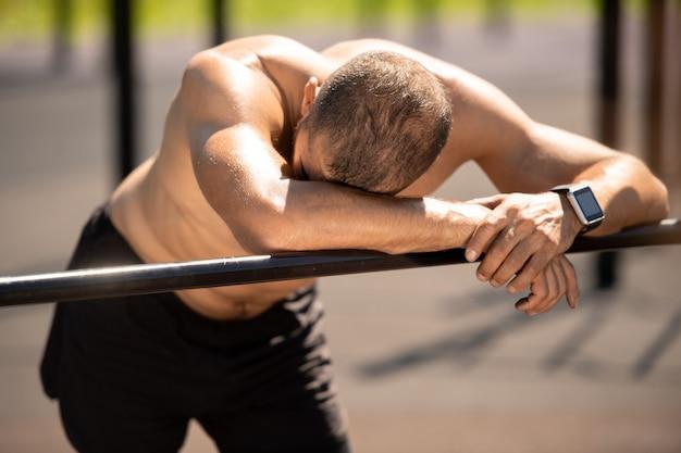 疲れている若いスポーツマンが腕をスポーツバーに置き、休息しながら頭の1つをスポーツバーに留める