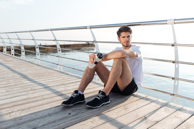 Tired young sportsman sitting on wooden terrace and relaxing