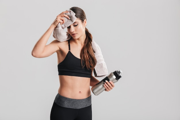 Tired young sportswoman in tracksuit drinking water and wiping sweat with towel after intensive workout, isolated over gray wall