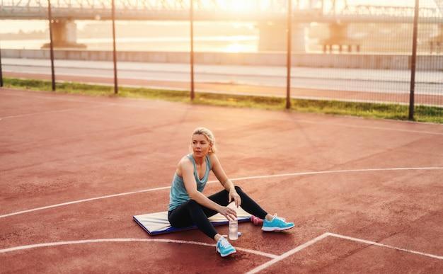ハードトレーニング後のトレーニングマットの外に座って疲れている若いスポーティなかわいいブロンドの女の子。早朝のトレーニング。