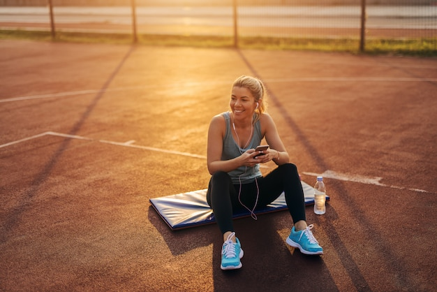 Tired young sporty cute blond girl sitting outside on a training mat after hard training and listening to the music.