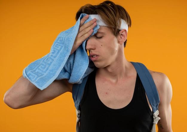 オレンジ色の壁に隔離されたタオルで額を拭くヘッドバンドとリストバンド付きのバックパックを身に着けている疲れた若いスポーティな男 無料写真
