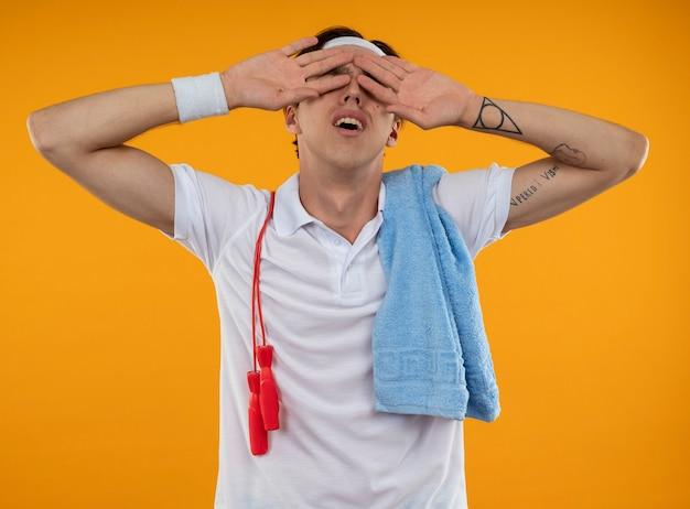 Усталый молодой спортивный парень в повязке на голову с браслетом со скакалкой и полотенцем на плече, положив руку на глаза