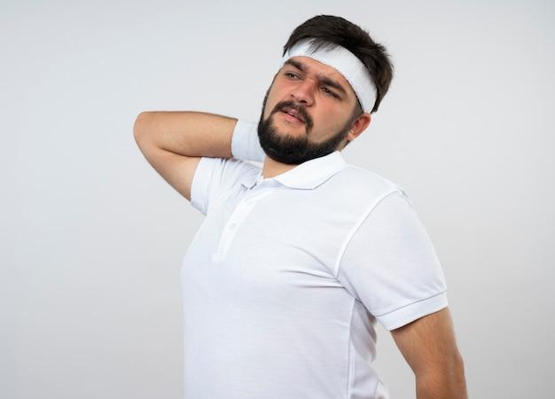 白い壁で隔離の首に手を置くヘッドバンドとリストバンドを身に着けている側を見て疲れた若いスポーティな男