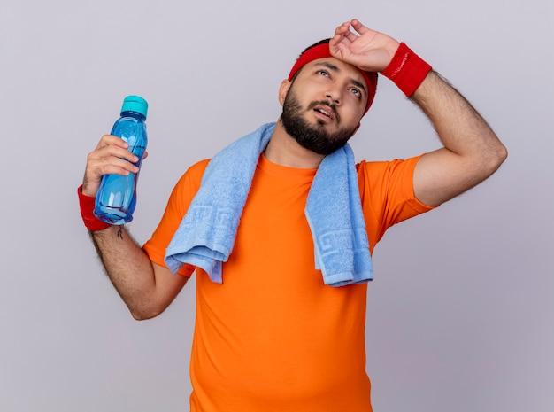 Stanco giovane sportivo da uomo che osserva in su che indossa la fascia e la fascia da polso tenendo la bottiglia di acqua con un asciugamano sulla spalla mettendo la mano sulla fronte isolati su sfondo bianco
