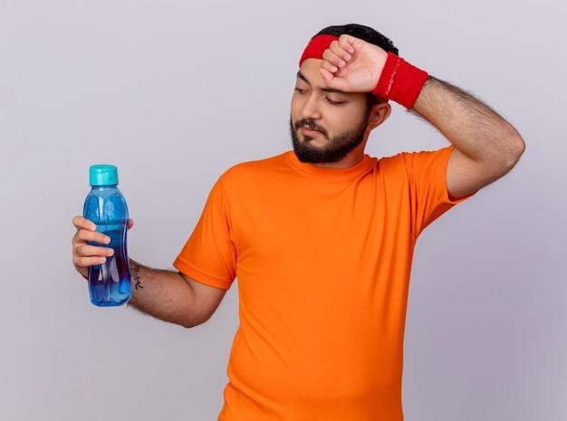 水のボトルを保持し、白い背景で隔離の手で額を拭くヘッドバンドとリストバンドを身に着けている疲れた若いスポーティな男