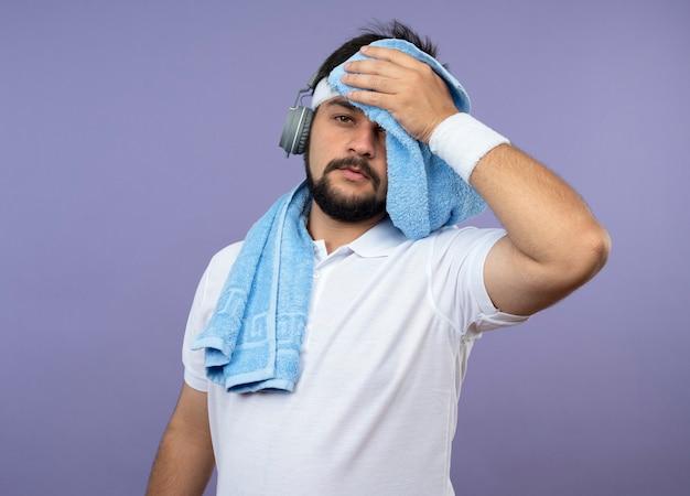 緑で隔離のタオルで額を拭くヘッドフォンでヘッドバンドとリストバンドを身に着けている疲れた若いスポーティな男