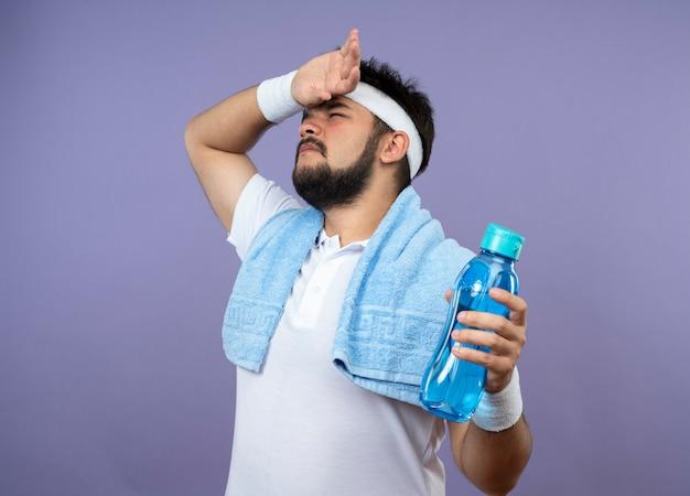 Stanco giovane uomo sportivo che indossa la fascia e il braccialetto tenendo la bottiglia d'acqua con un asciugamano sulla spalla, asciugandosi la fronte con la mano