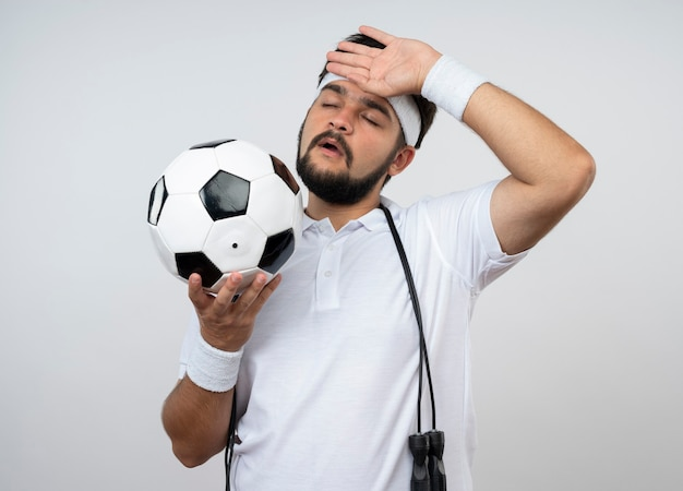 Tired young sporty man with closed eyes wearing headband and wristband with jump rope on shoulder holding ball putting hand on forehead isolated on white wall