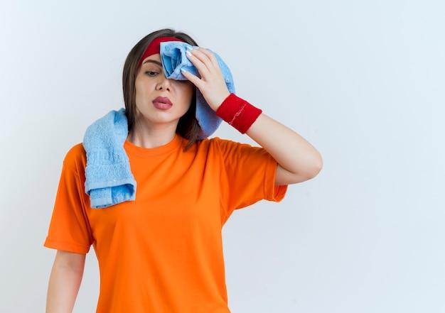 Усталая молодая спортивная женщина с повязкой на голову и браслетами с полотенцем на шее смотрит вниз, вытирая пот полотенцем
