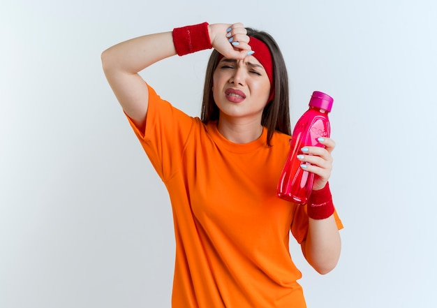 Tired young sporty woman wearing headband and wristbands holding water bottle  touching forehead isolated on white wall with copy space