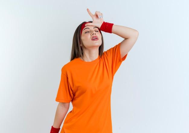 Stanco giovane donna sportiva che indossa la fascia e braccialetti guardando il lato ammiccante facendo gesto perdente isolato