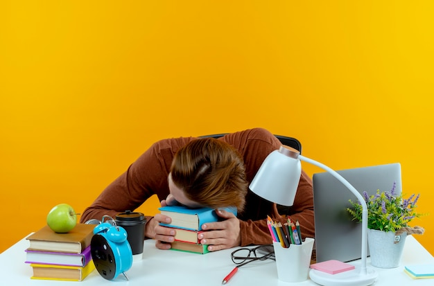 Tired young student boy sitting at desk with school tools putting head on books isolated on yellow wall