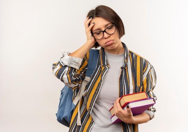 Ragazza giovane studente stanco con gli occhiali e borsa posteriore che tengono i libri mettendo la mano sulla testa con gli occhi chiusi isolati su priorità bassa bianca