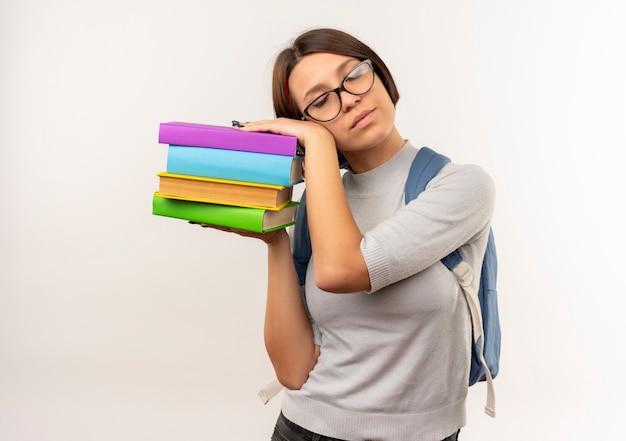Ragazza giovane studente stanco con gli occhiali e borsa posteriore che tengono i libri e mettendo la testa su di loro cercando di dormire isolato su priorità bassa bianca