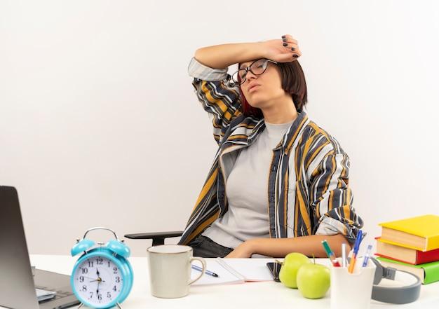 흰색 배경에 고립 된 닫힌 된 눈으로 이마에 팔을 넣어 대학 도구로 책상에 앉아 안경을 쓰고 피곤 된 젊은 학생 소녀