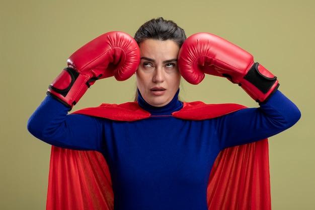 Stanco giovane ragazza del supereroe che indossa i guantoni da boxe mettendo le mani sul tempio isolato su verde oliva