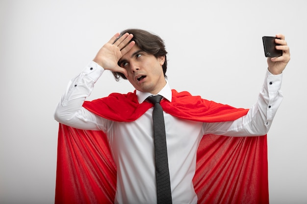 ネクタイを身に着けている疲れた若いスーパーヒーローの男は、自分撮りを取り、白で隔離の頭に手を置く